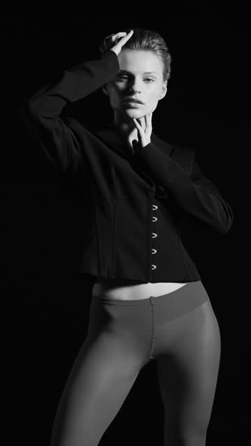 Blonde girl stands in a black jacket and tights, touches her face and hair with her hands. Black and white video. video