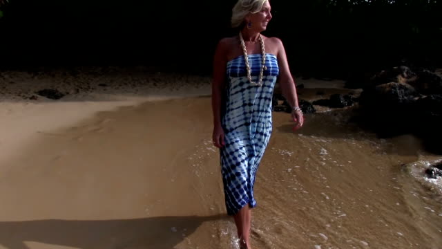Blonde girl walks on beach in Hawaii video
