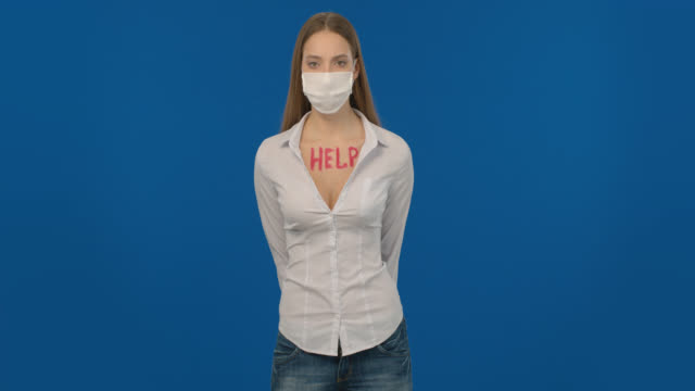 A blonde girl wearing a white shirt, wearing a mask, protects herself from COVID-19 and asks for help. video