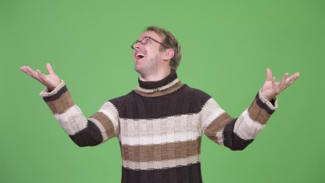 Blonde handsome man ready for winter Studio shot of blonde handsome man wearing turtleneck sweater ready for winter against chroma key with green background catching stock videos & royalty-free footage