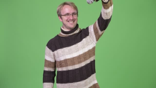 vídeos de stock e filmes b-roll de blonde handsome man using microphone and ready for winter - weatherman