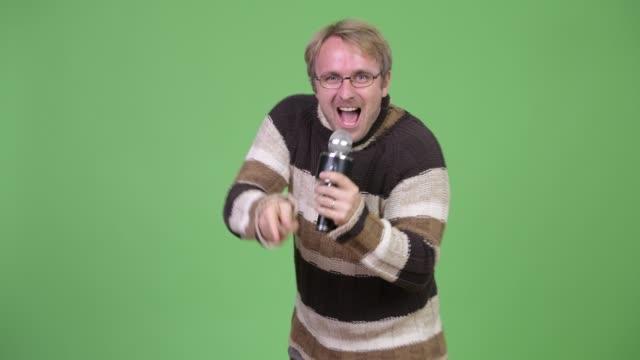 Homem considerável louro que usa o microfone e pronto para o inverno - vídeo
