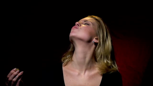blonde in a black sweater bites a jellyworm - top nero video stock e b–roll