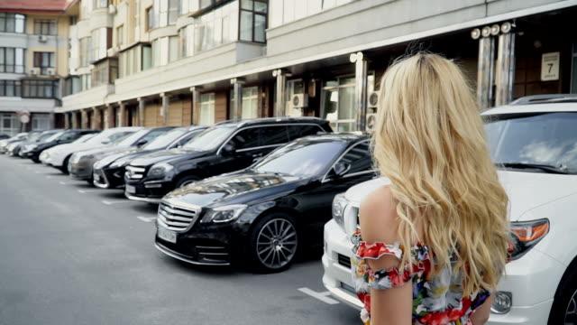 vídeos y material grabado en eventos de stock de rubia con un vestido de verano posando en el estacionamiento. cableado de la cámara. gait femenino - ojo morado