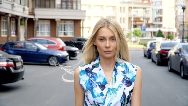 vídeos y material grabado en eventos de stock de rubia en un traje de verano posando en el estacionamiento. cableado de la cámara. caminata de mujeres - ojo morado