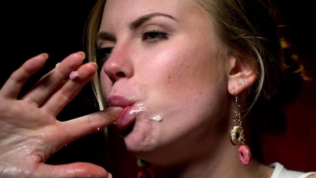 stockvideo's en b-roll-footage met blonde in een wit t-shirt duwt een donut met haar vingers in haar mond, langzame motie - wit t shirt