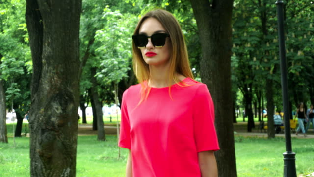 blonde in red suit and sunglasses walks in the park video