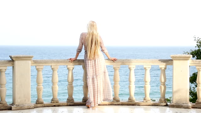 blonde is standing on the balcony and looking at the sea - balaustrata video stock e b–roll