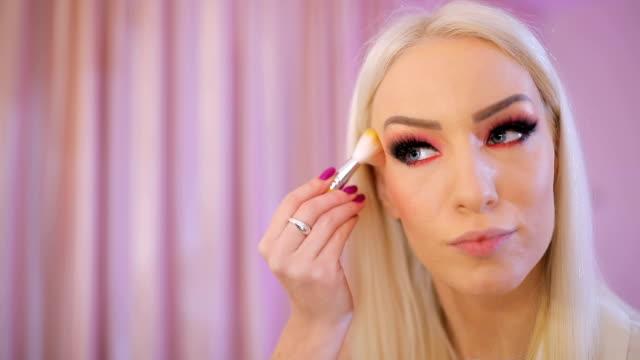 Blonde lady applying make up