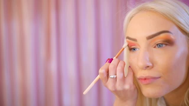 Blonde lady applying make-up on eyes
