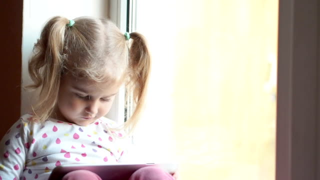Blonde little girl using tablet pc. Sitting on the window sill. Child smiling and looking at camera. Child plays on the PC video