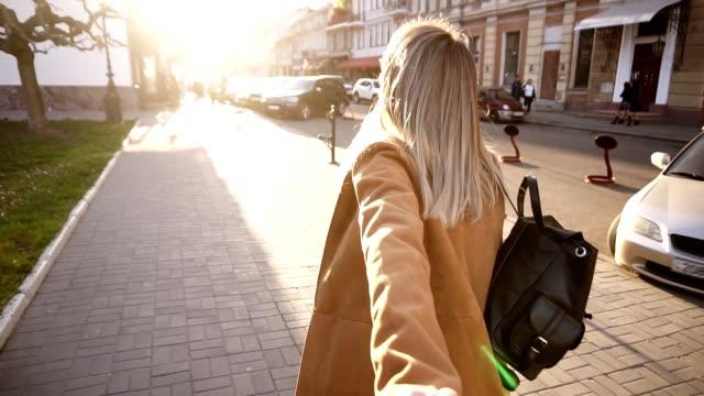blond långhårig flicka i beige päls går genom staden full av solljus. flickan drar killens hand. kvinna och man på dejt. lovers hålla händerna - pojkvän bildbanksvideor och videomaterial från bakom kulisserna