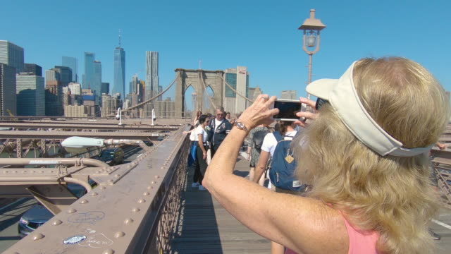 Blonde middle aged Woman taking photos on her cell phone on Brooklyn Bridge pedestrian walkway view of New York City financial district skyline, Manhattan, New York and traffic passing below Blonde middle aged Woman taking photos on her cell phone on Brooklyn Bridge pedestrian walkway view of New York City financial district skyline, Manhattan, New York and traffic passing below 19th century style stock videos & royalty-free footage