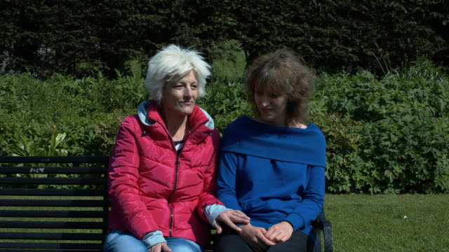 A Blonde Mother In Her 40s And Her Daughter Sitting On A Bench In The Park video
