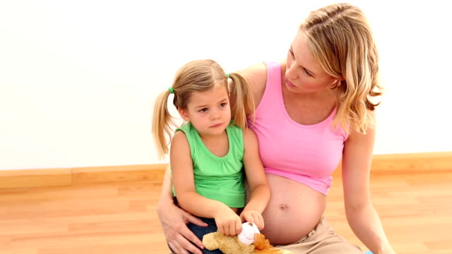 Blonde pregnant woman sitting with her little girl Blonde pregnant woman sitting with her little girl in a fitness studio pigtails stock videos & royalty-free footage