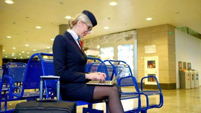 Blonde stewardess sitting in departure hall chatting on laptop video