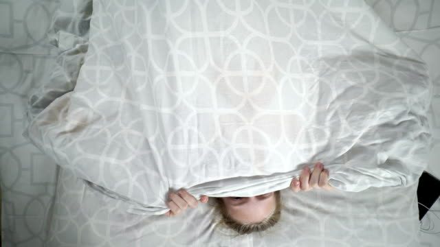 Blonde teenage girl lying in bed under blanket hiding her face with a smile video