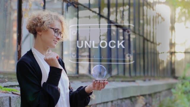 ブロンドはホログラムロック解除を使用しています - なりすまし犯罪点の映像素材/bロール