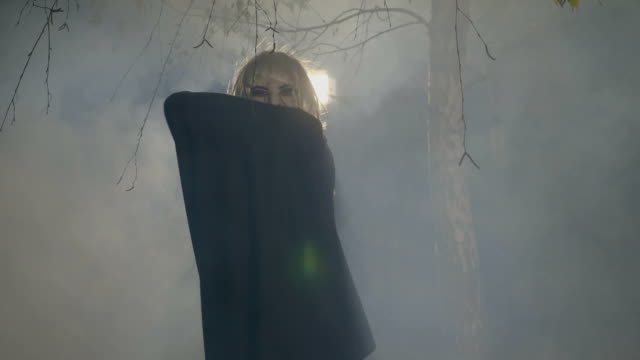 Blonde vampire uncovering his mantle and preparing to attack in the forest on halloween night video