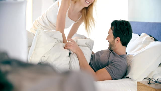 Blonde woman and man joking and pillow fighting. Couple in love morning wake up at home in bedroom. Caucasian girlfriend and boyfriend people liying on bed. Lovely strokes. 4k video video