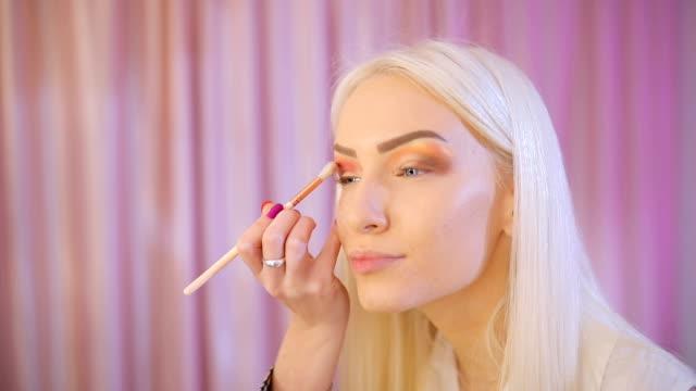 Blonde woman applying make-up on eyes