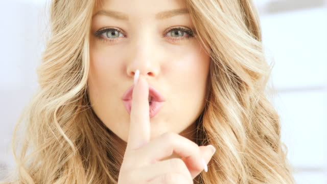 blonde woman doung shh with finger on her lips and then smiling blonde woman doung shh with finger on her lips and then smiling highlights hair stock videos & royalty-free footage