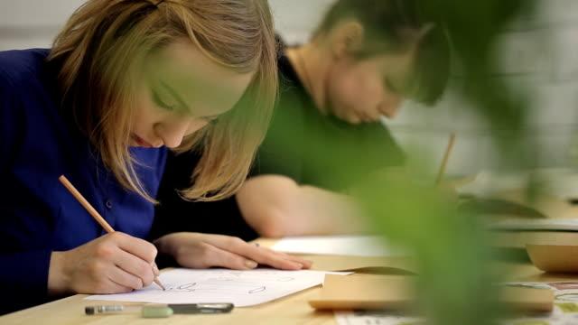 Mulher loira desenha pelo desenho a lápis na mesa de madeira - vídeo