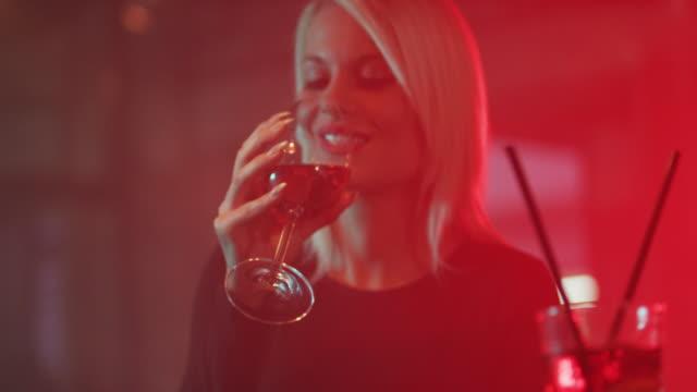 Blonde woman drinking red wine 4K