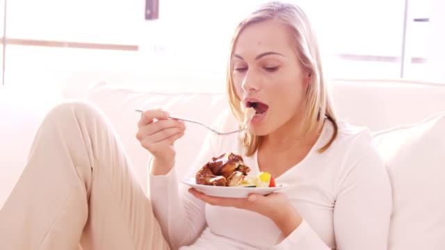 Blonde Frau essen Huhn auf einem sofa – Video