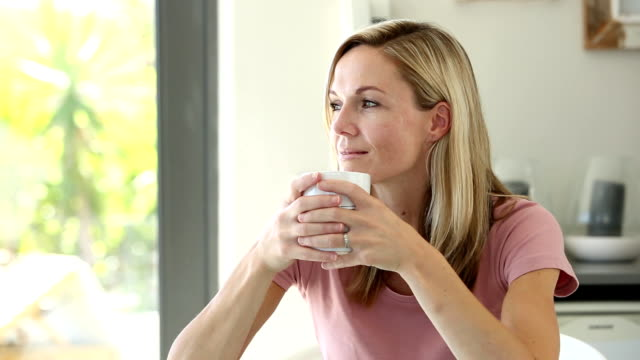 Blonde woman enjoying her drink video