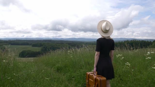 blonde frau in schwarzem kleid und koffer zu fuß auf wiese mit bergen auf dem hintergrund - kopfbedeckung stock-videos und b-roll-filmmaterial