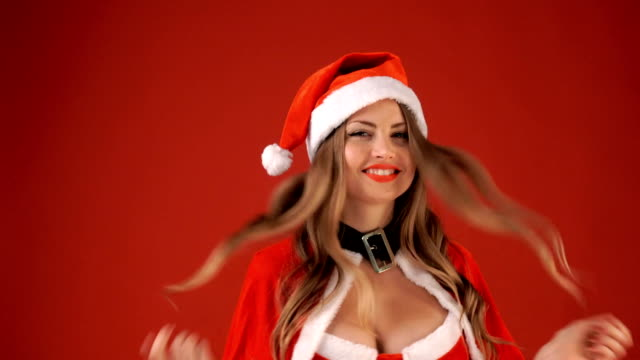 blonde woman in clothes of Santa Claus smiling on red background video