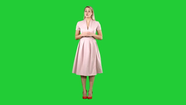 Blonde woman in pink clothes talking to camera on a Green Screen, Chroma Key Full length portrait. Blonde woman in pink clothes talking to camera on a Green Screen, Chroma Key. Professional shot in 4K resolution. 005. You can use it e.g. in your commercial video, business, presentation, broadcast full length stock videos & royalty-free footage