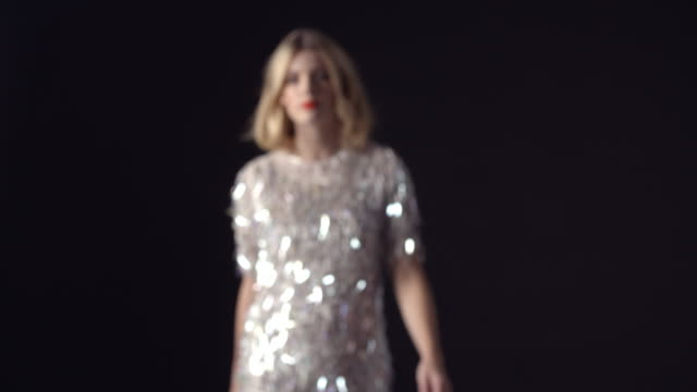 Blonde woman in sparkly dress walking to camera, into focus