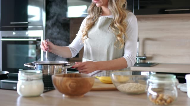 blonde woman in the kitchen making oatmeal for breakfast - articoli casalinghi video stock e b–roll