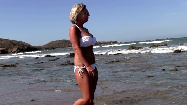 Blonde woman in white bikini walking on beach and rocks video