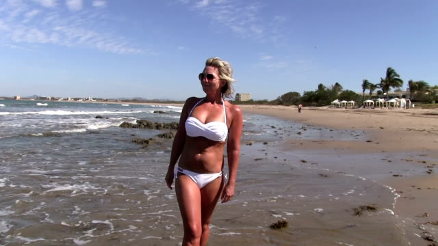 Blonde woman in white bikini walking on beach facing front video