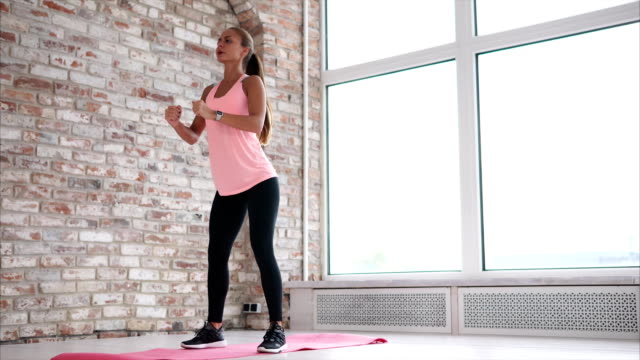 vídeos de stock e filmes b-roll de blonde woman is doing morning exercise in modern interior of large room - agachar se