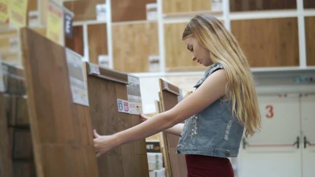 vídeos de stock e filmes b-roll de blonde woman is touching a large wooden panel for floor coverings in a store - material de construção