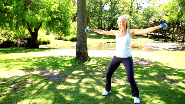 Blonde woman lifting dumbbells in the park video