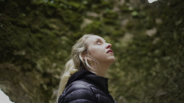 Blonde woman looking around inside a cave Outdoor and nature details of Lisbon, Portugal cave stock videos & royalty-free footage