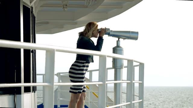 Blonde woman looking through tourist binoculars at seascape. Slow motion. HD