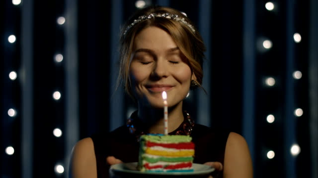 blonde-woman-making-wish-and-blowing-candle-on-birthday-cake-happy-video-id626322856?s=640x640