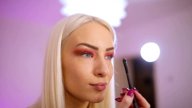 Blonde woman putting make-up on eyes One woman, make up artist tutorial, applying make up on face. eyeliner stock videos & royalty-free footage