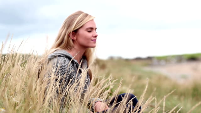 Blonde woman relaxing in the dunes in cinemagraph video