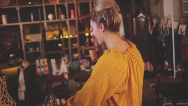 Blonde woman shopping for swimsuits in a vintage boutique store