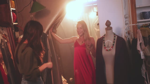 Blonde woman showing dress to friend in boutique store