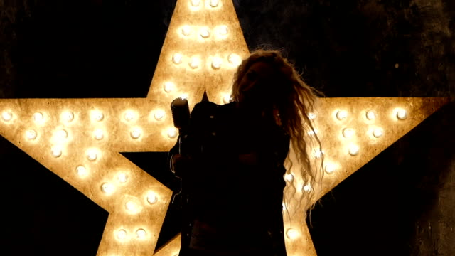 blonde woman singer with microphone, shining star in the background. slow motion, silhouette - steampunk fashion stock videos and b-roll footage
