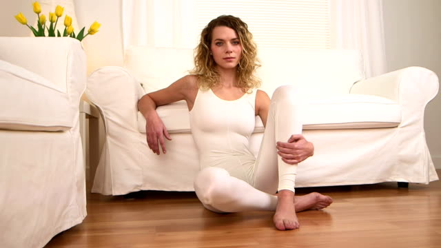 Blonde woman sitting on floor after yoga medium shot, dolly shot leotard stock videos & royalty-free footage