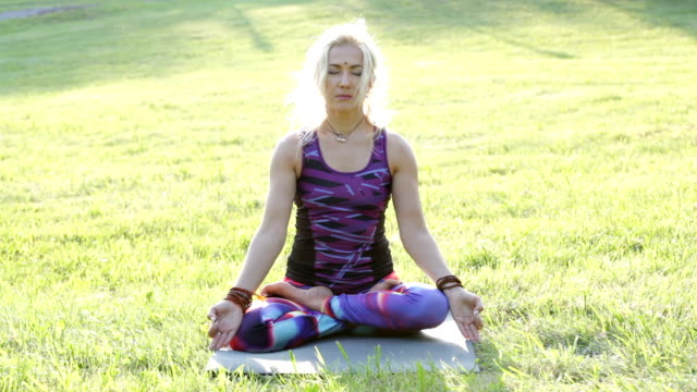 blonde woman sitting on the mat on the grass in meditation - mudra video stock e b–roll